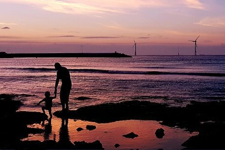 A view of an adult with a child walking on the beach at sunset