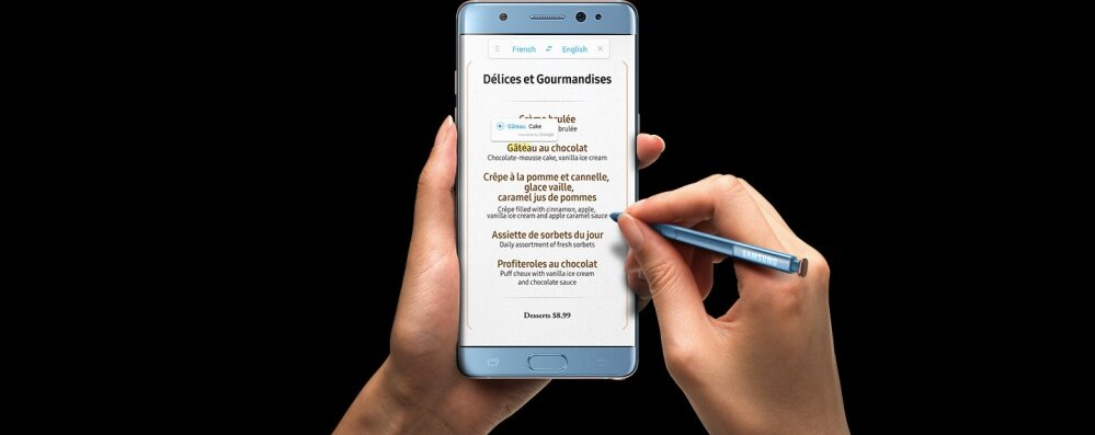 Left Hand clutching the Galaxy Note FE Black Onyx with S Pen Translation on a French menu